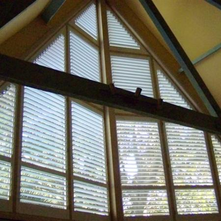 A fine example of Shutterkits Specialty Shutters. What an amazing window and a difficult one to decide on the best window covering. Arthur has done an awesome job - painting, assembling and installing these angle shutters. Arthur chose a clearview rotation system so as to not interfere with the clean lines of the room. They look very effective.