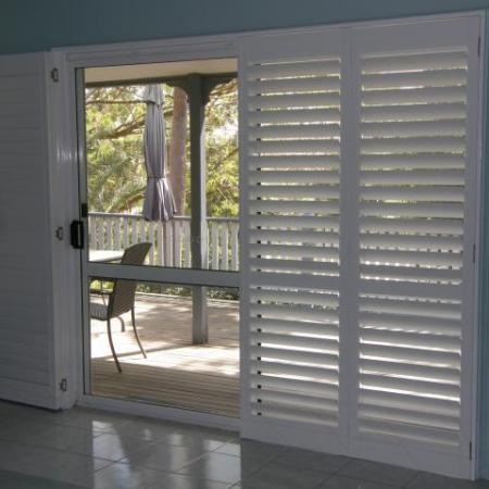 Stylish in white: Plantation Shutters look good in any location. Leah's Painted Shutters brightens the room dramatically and contrasts well against the dark furniture.